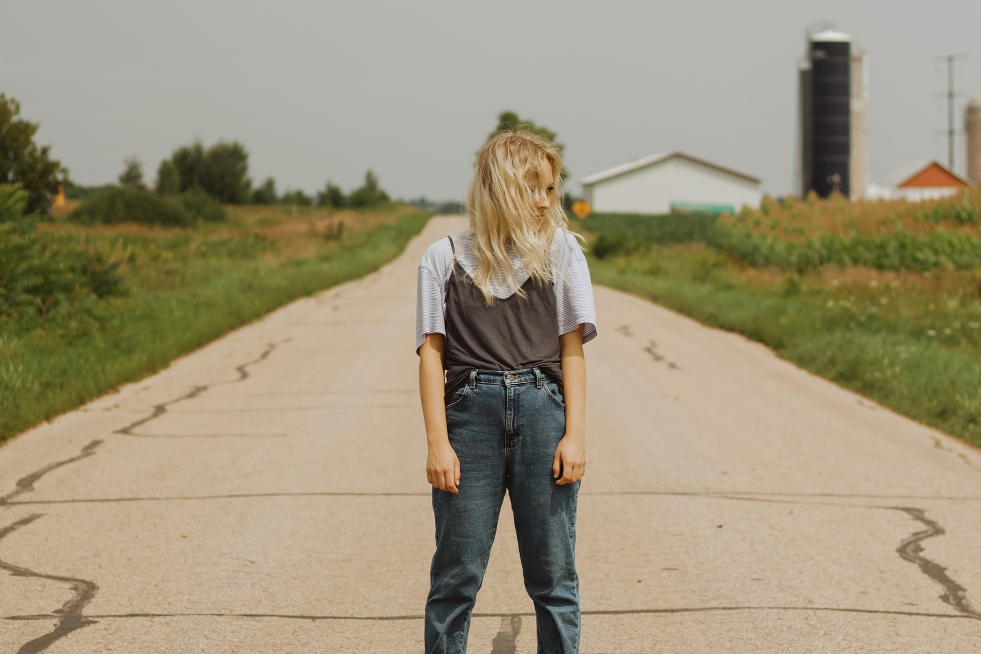 woman in white t-shirt and blue denim jeans walking on gray concrete road during daytime