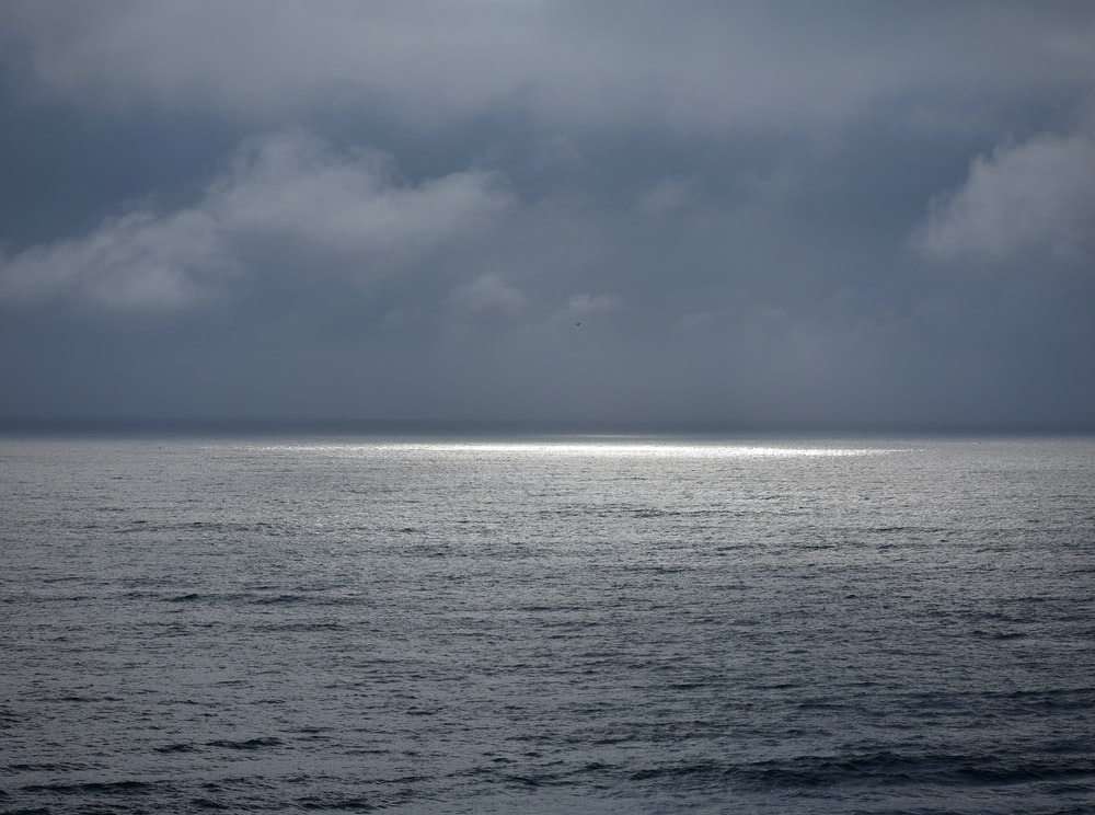 body of water under cloudy sky during daytime