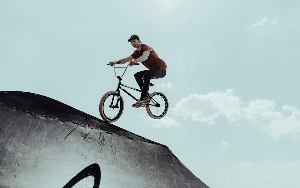 man in orange shirt riding on black bmx bike