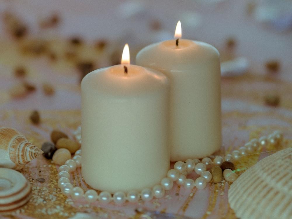 white pillar candle on white table cloth