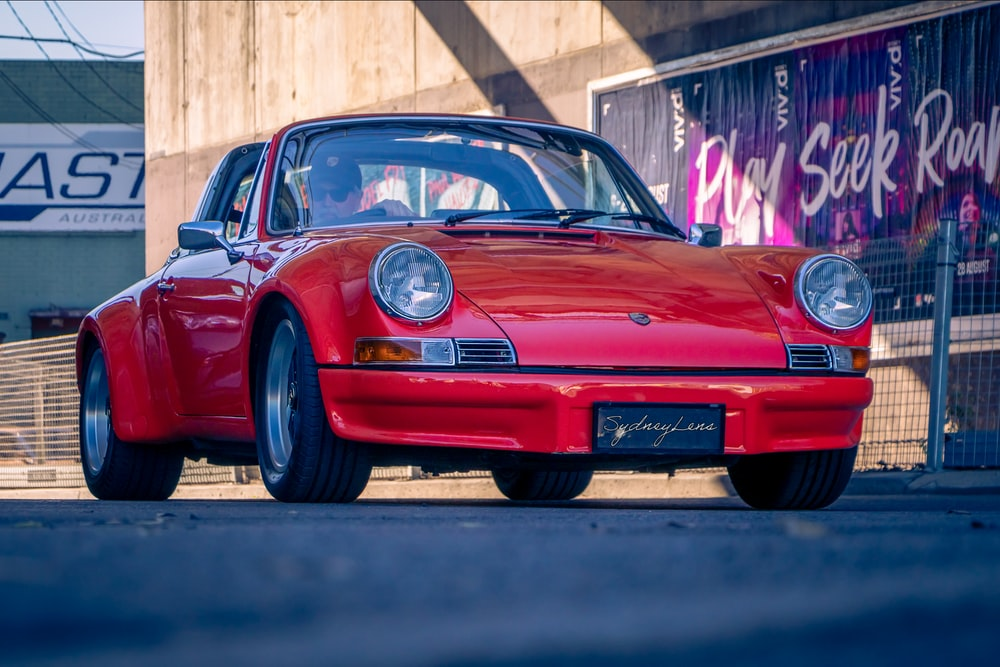 red porsche 911 parked on road during daytime
