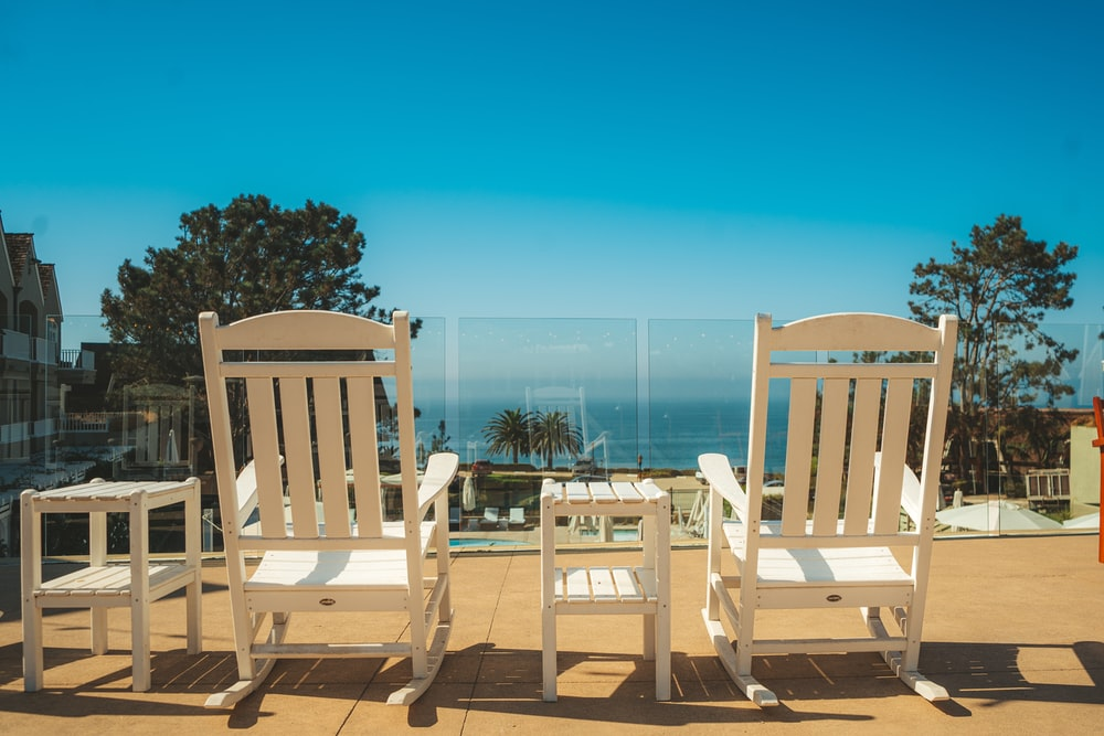 white wooden chairs on brown wooden deck during daytime