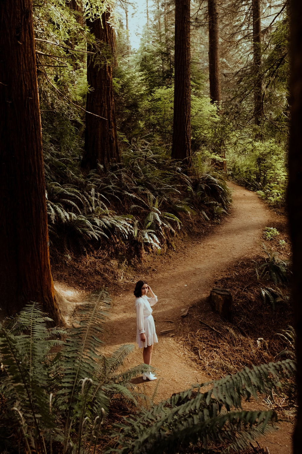 girl in white shirt walking on dirt road between green plants and trees during daytime