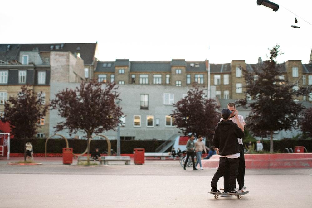 man in black coat and black pants walking on sidewalk during daytime