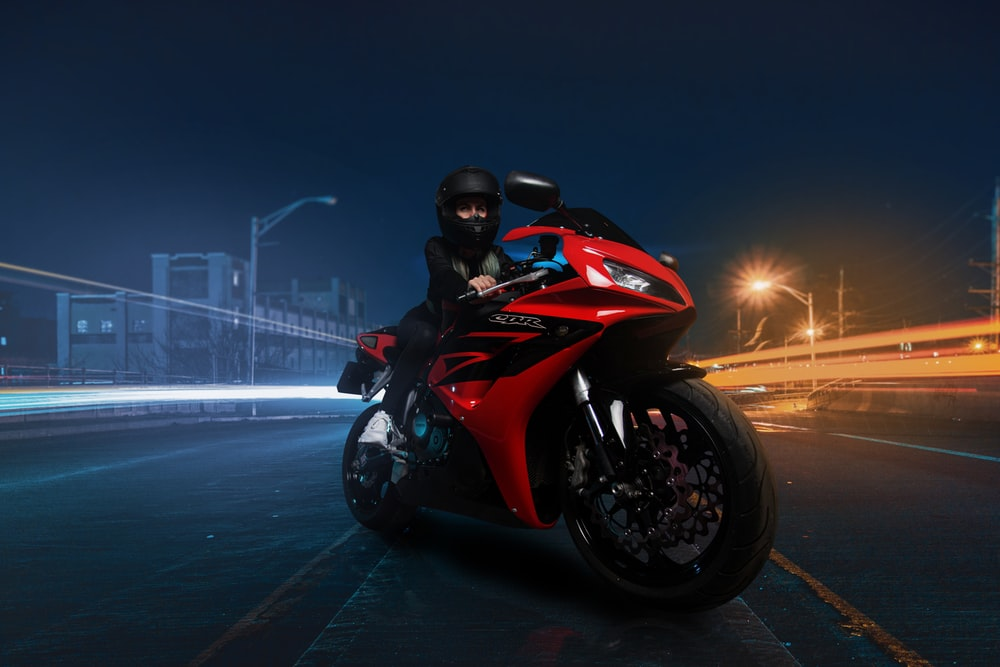 red and black sports bike on road during nighttime
