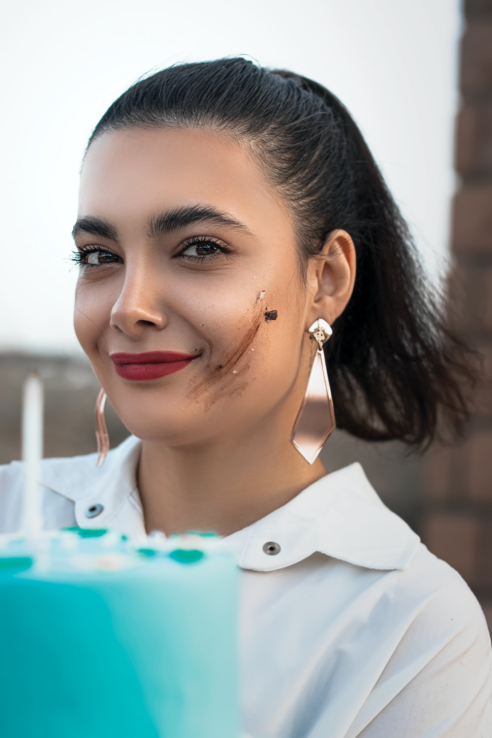 woman in white collared shirt with silver earrings