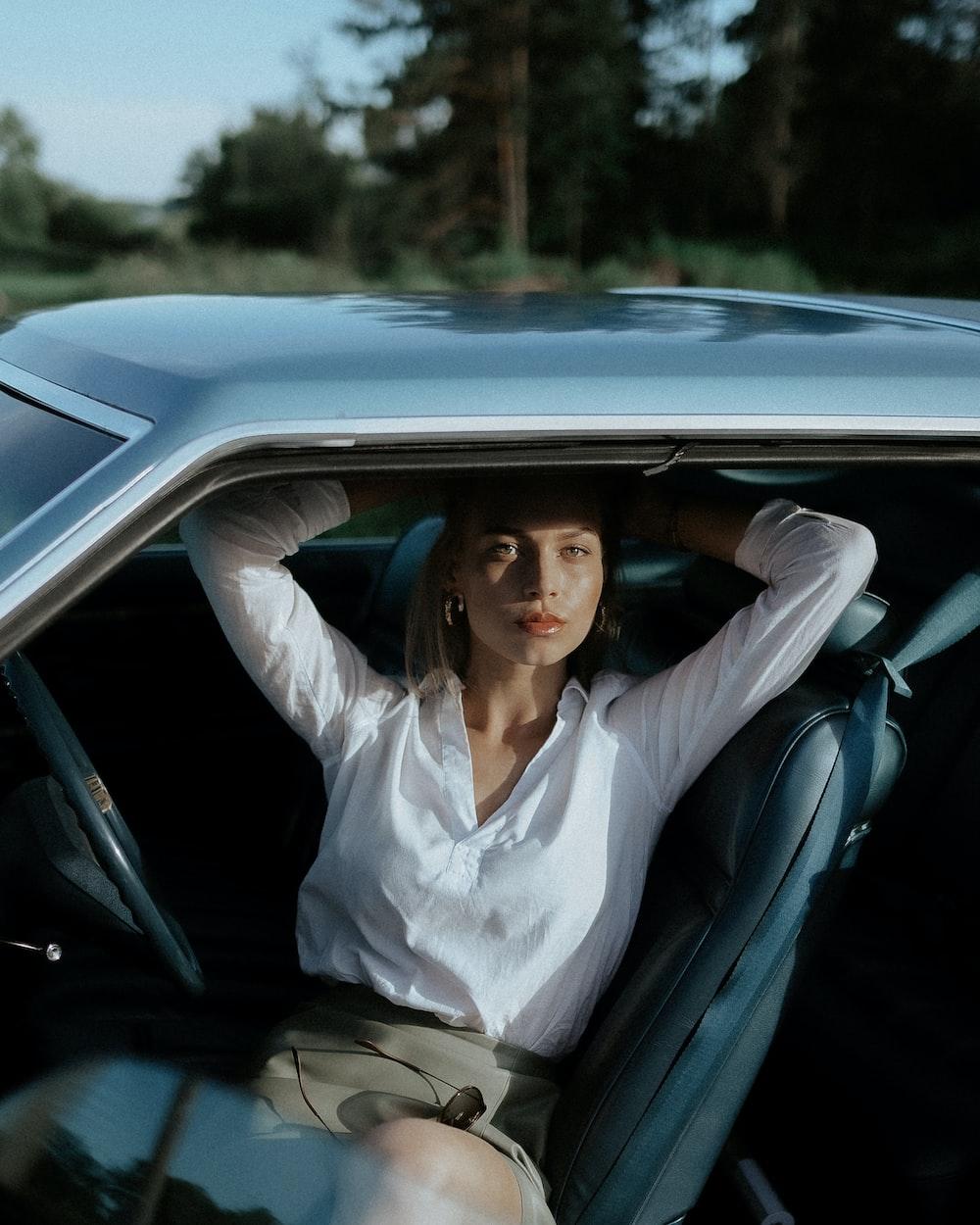 woman in white dress shirt sitting on car seat