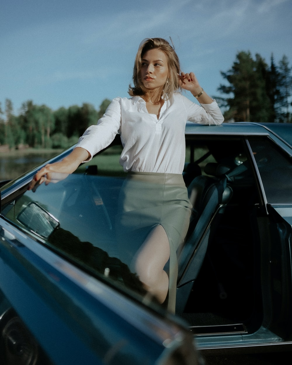 woman in white long sleeve shirt and gray skirt sitting on blue car