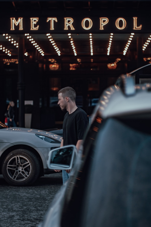 man in black jacket standing beside car during night time