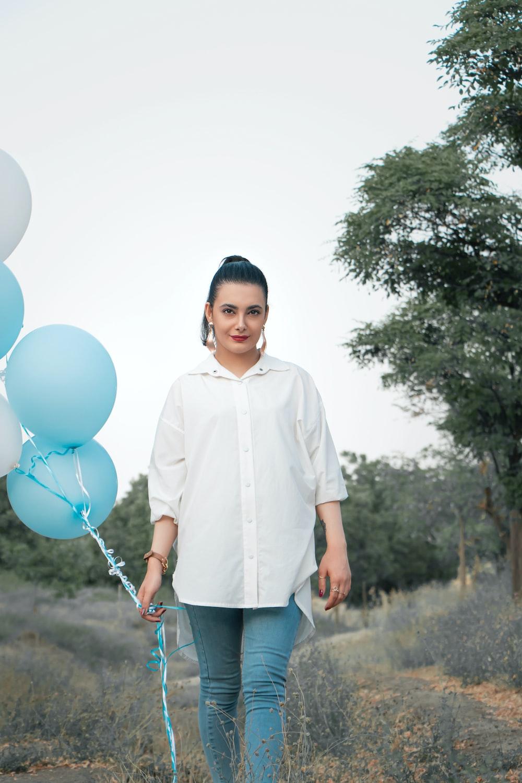 boy in white dress shirt holding blue balloons