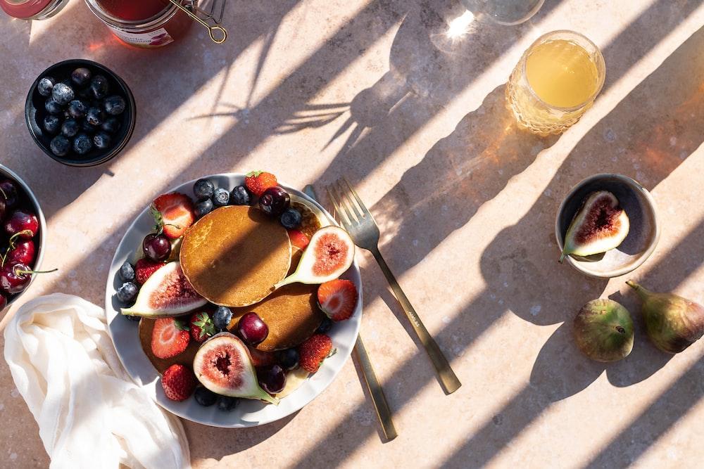 sliced strawberries and blueberries on white ceramic bowl
