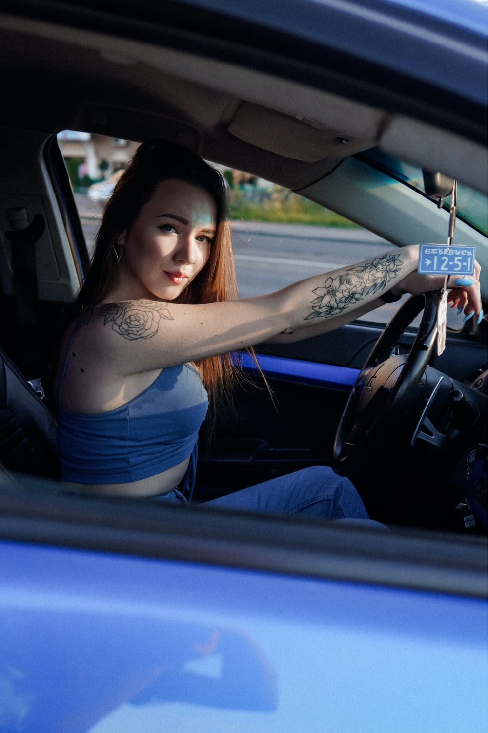 woman in blue tank top and blue denim jeans sitting on car seat