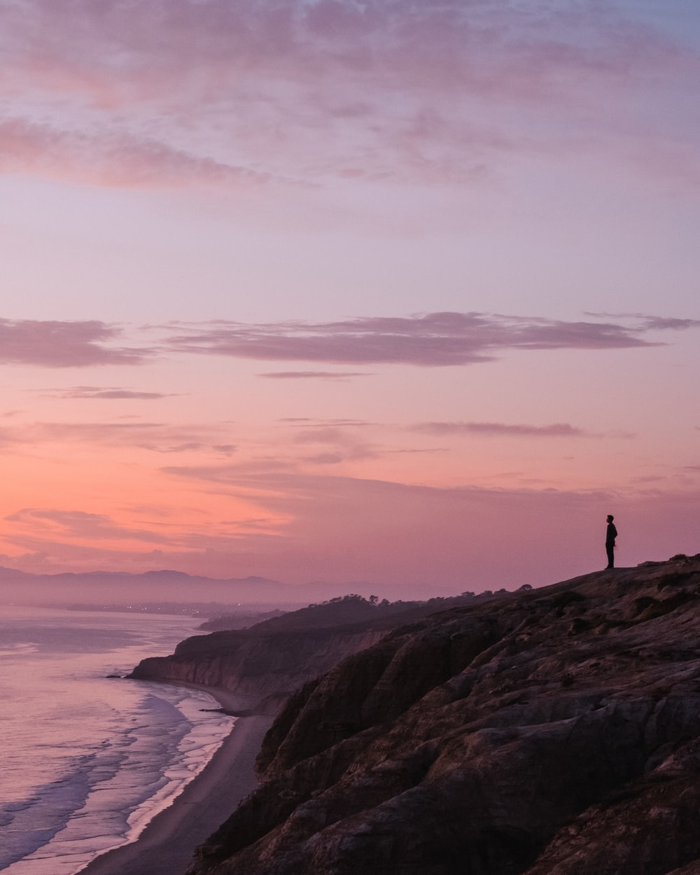 silhouette of person standing on rock formation near body of water during sunset