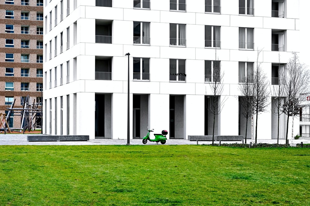 person in green shirt sitting on green grass field near white concrete building during daytime