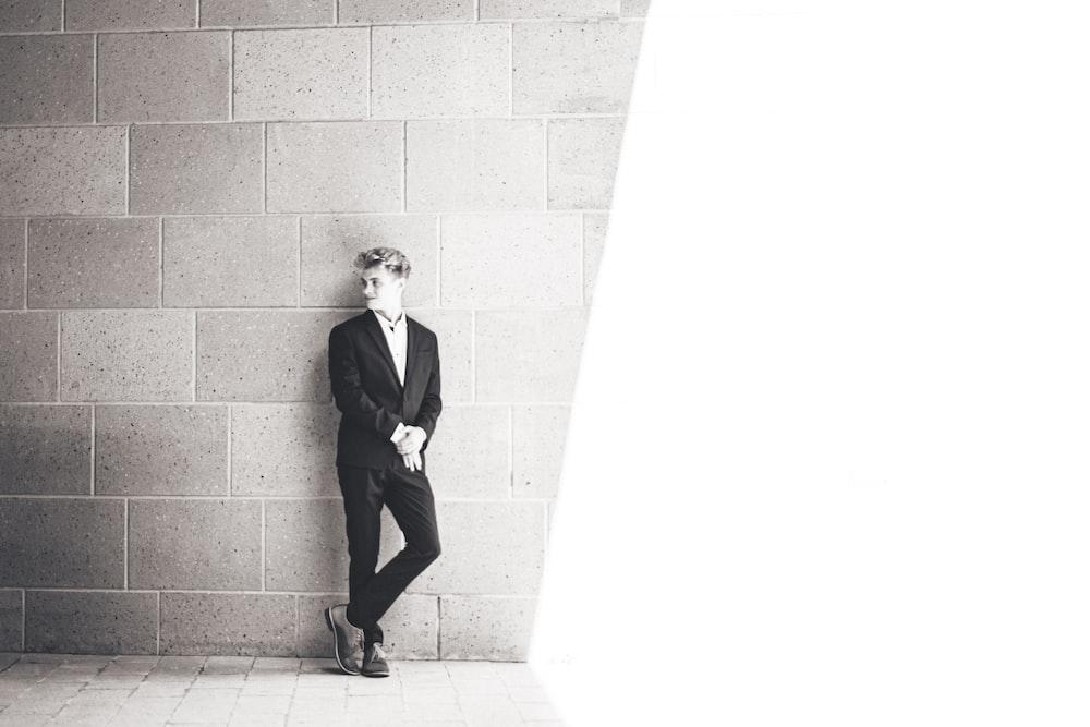 man in black suit standing beside wall