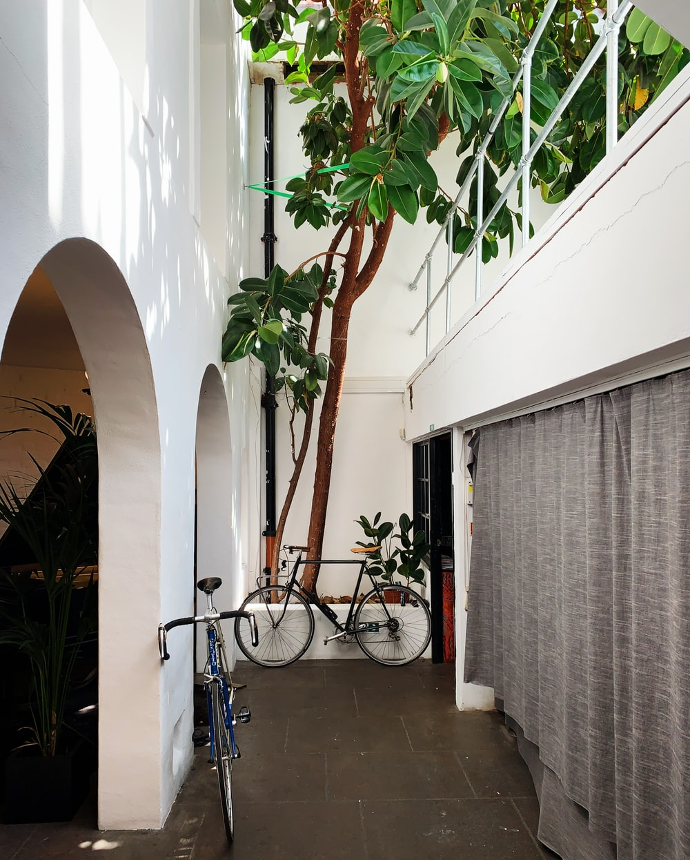 black bicycle parked on white concrete building