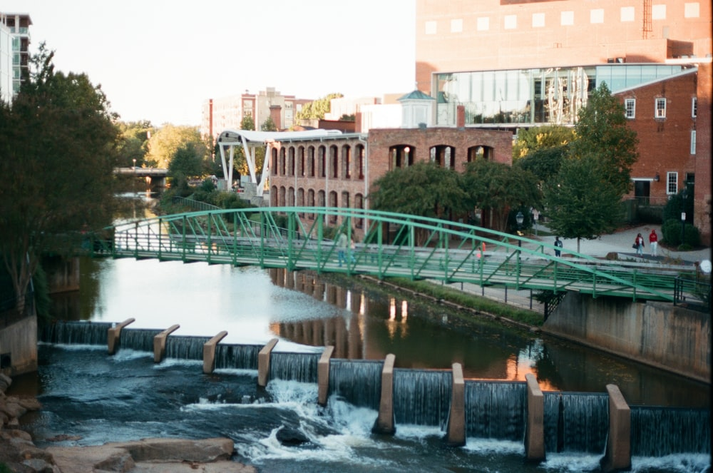 water falls near green bridge during daytime