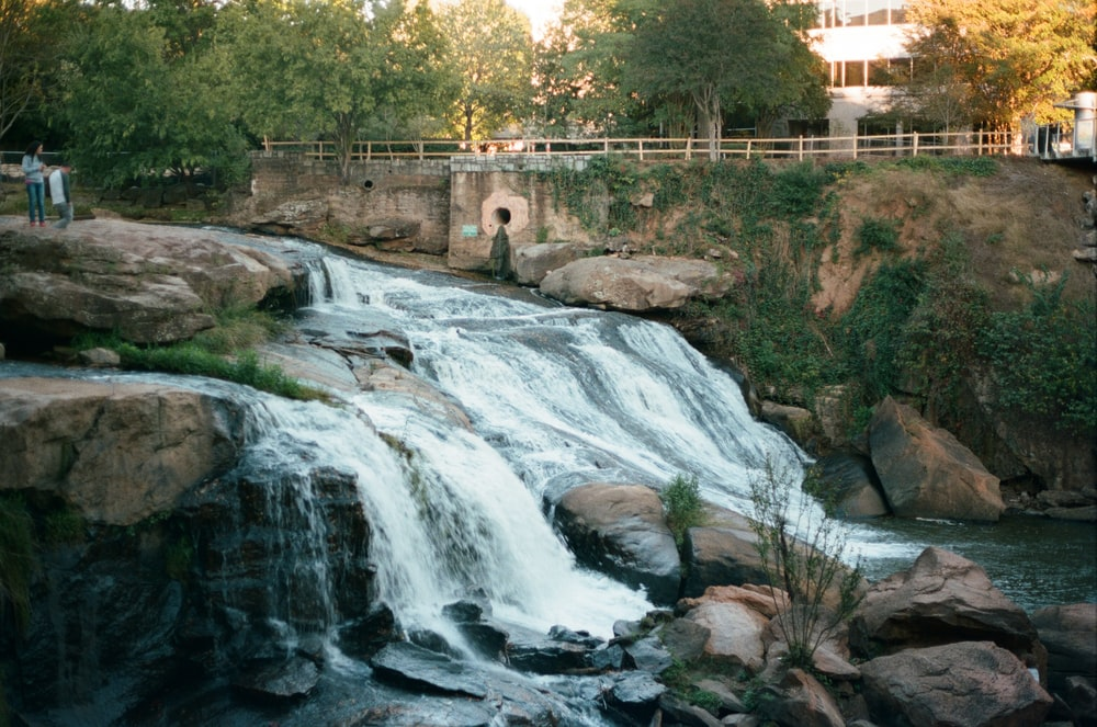 water falls near green trees during daytime