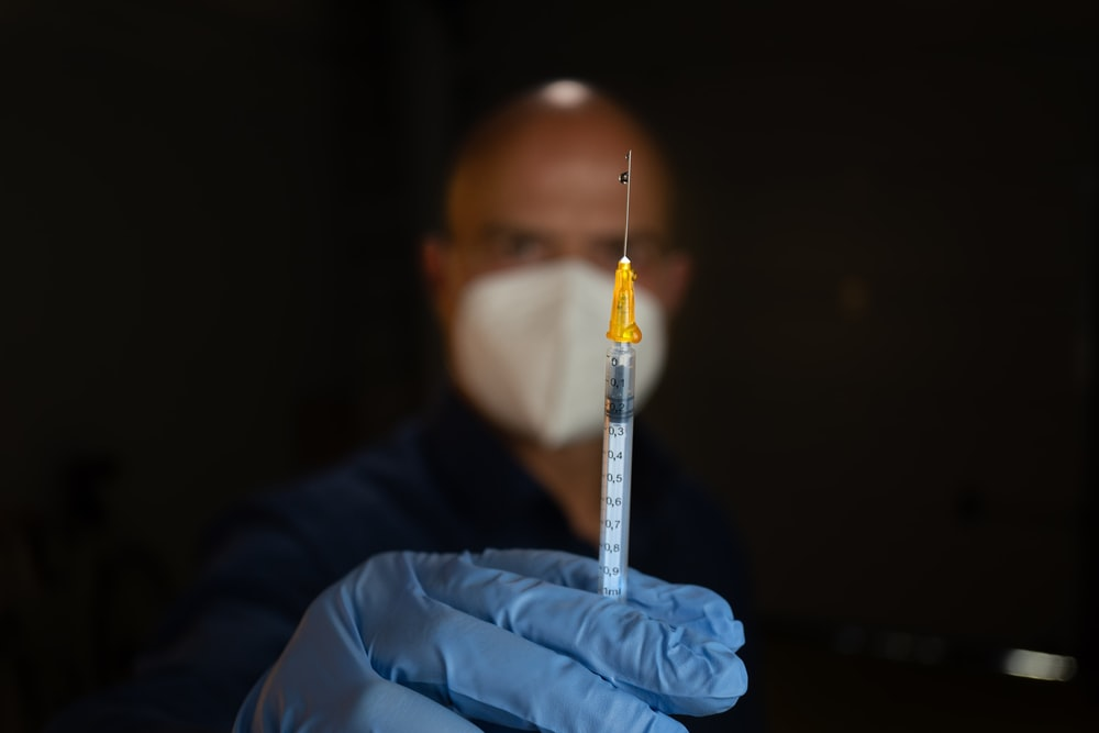 white and clear syringe on blue textile