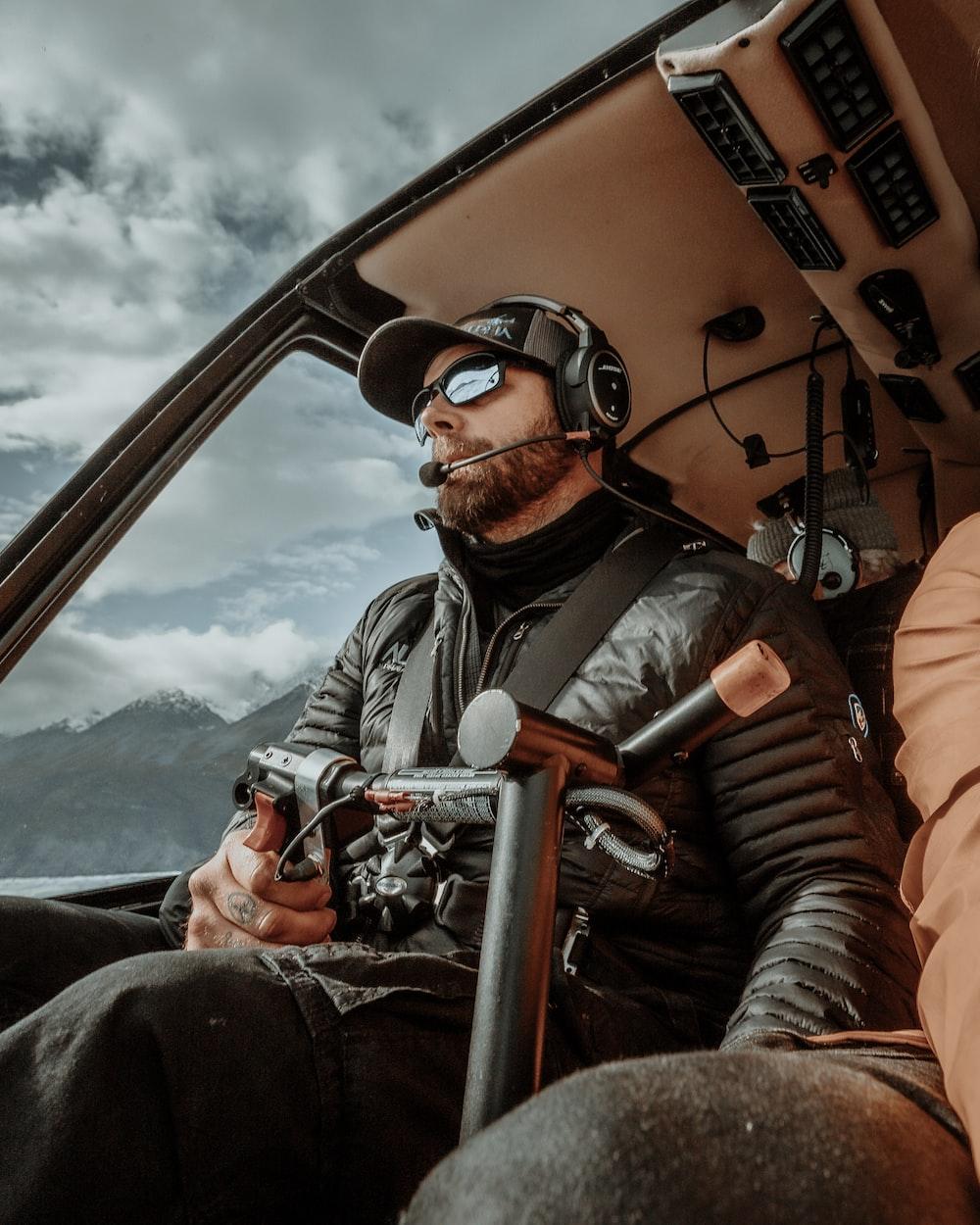 man in gray jacket wearing black sunglasses sitting on orange car seat during daytime