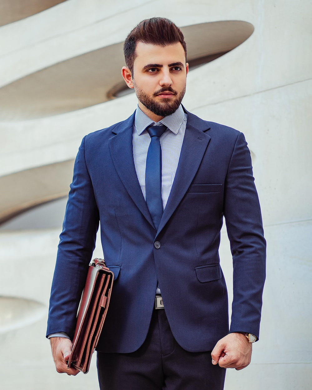 man in black suit jacket holding brown leather bag
