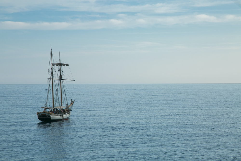 black sail boat on sea under white clouds during daytime