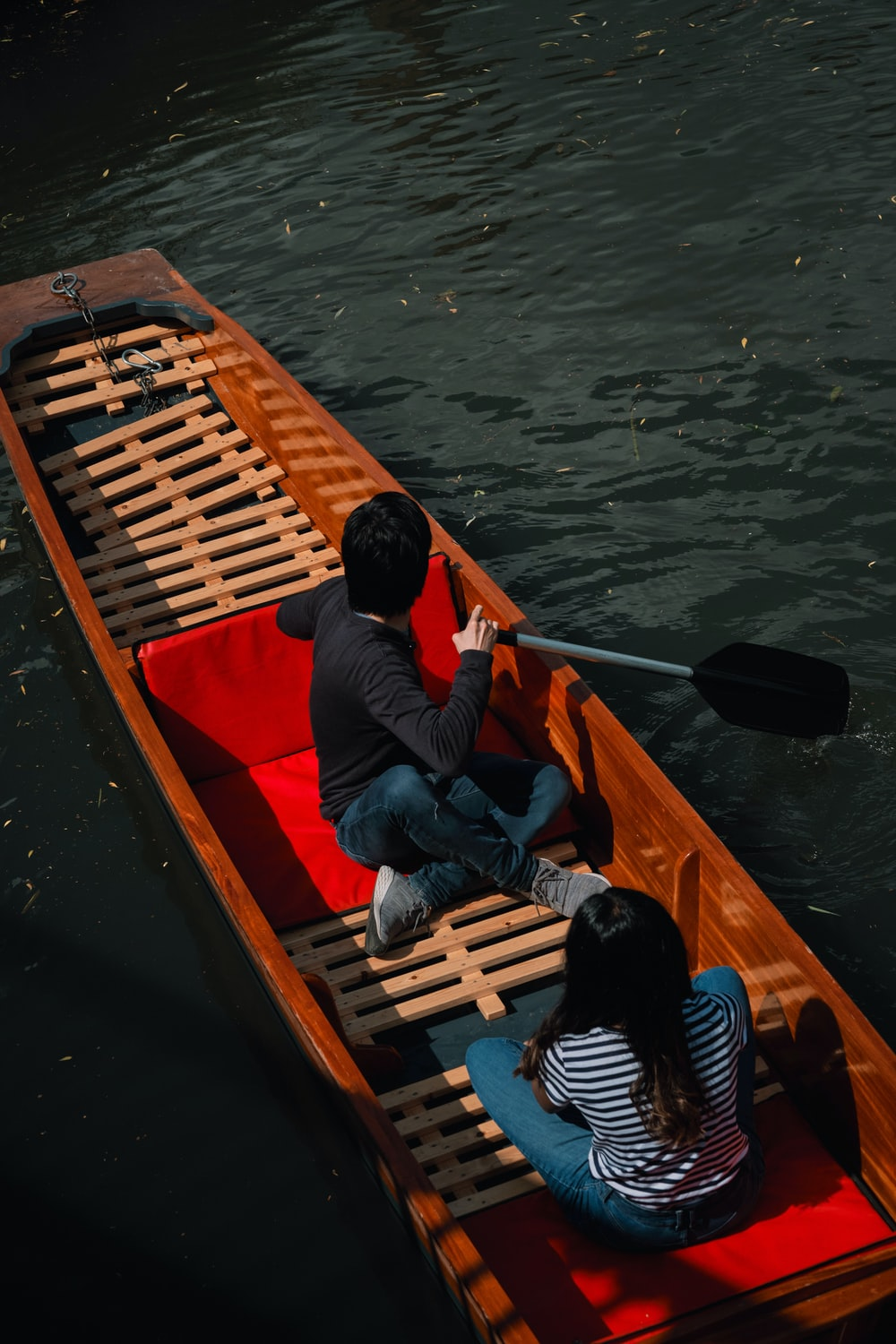 man in red shirt and blue denim jeans sitting on brown wooden boat