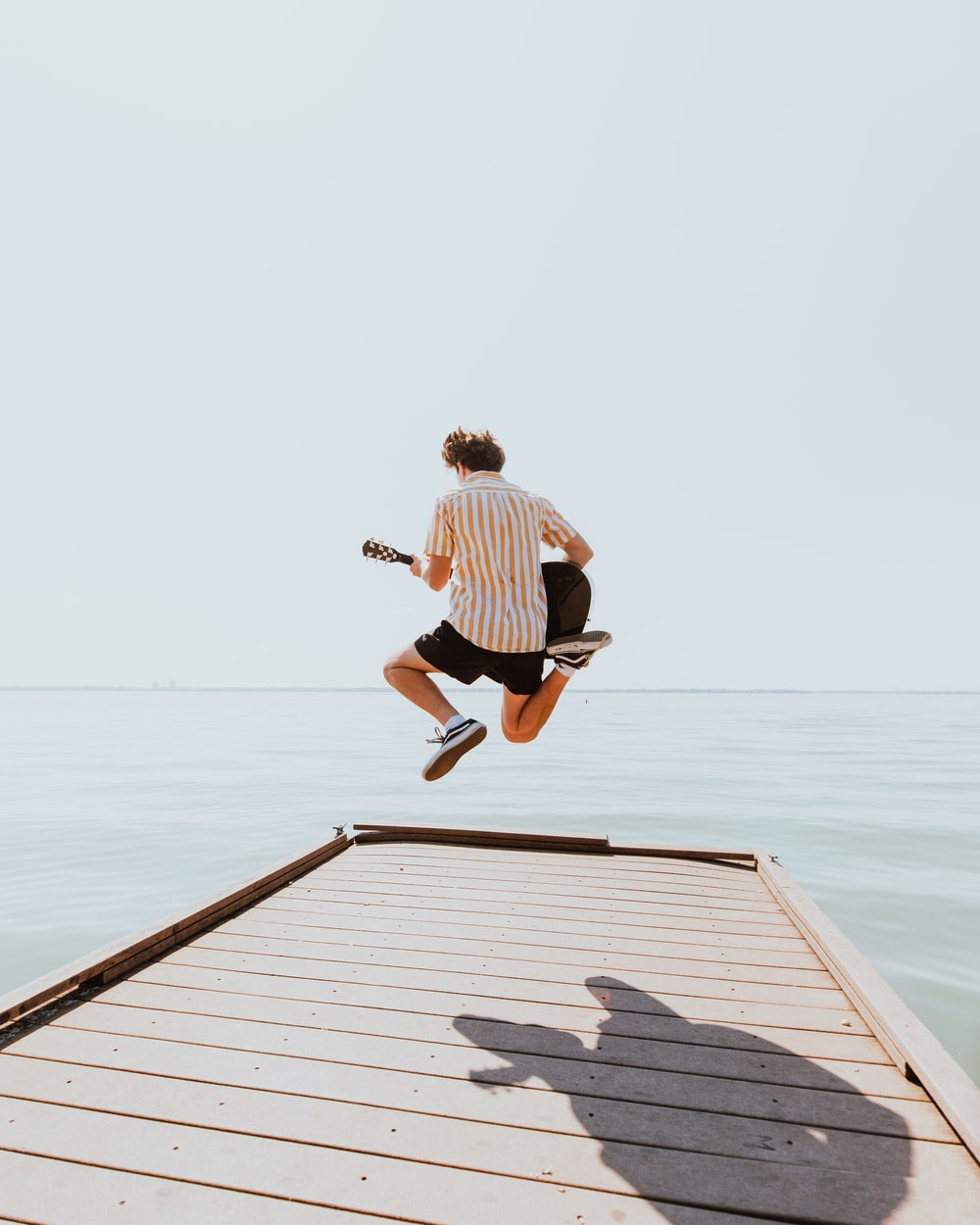 man in white and black stripe shirt and black shorts jumping on dock during daytime