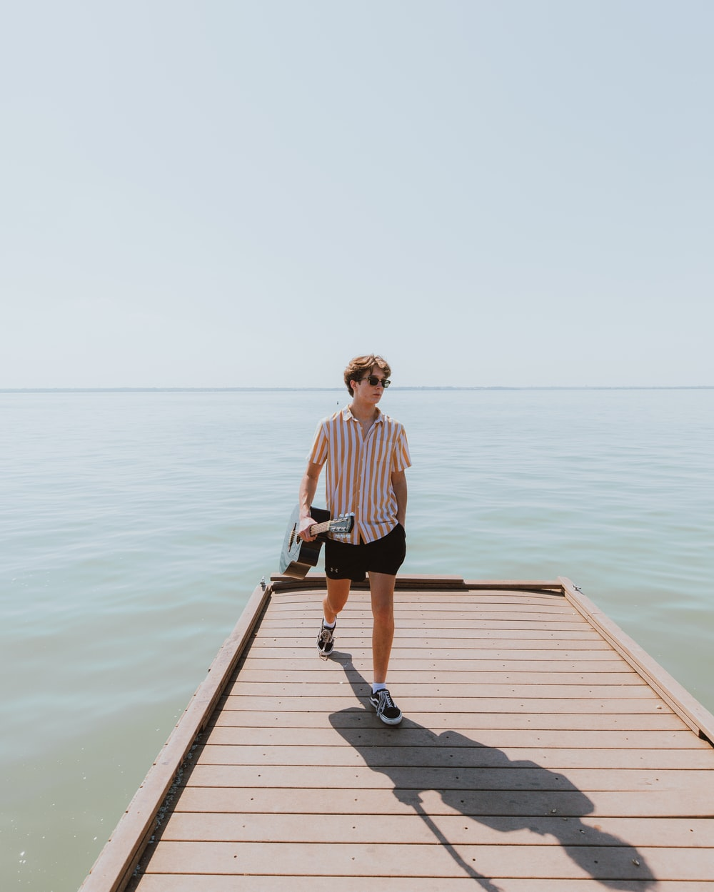 woman in black and white stripe shirt standing on dock during daytime