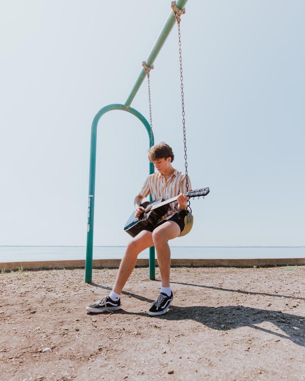 man in white t-shirt and red shorts sitting on green metal swing during daytime