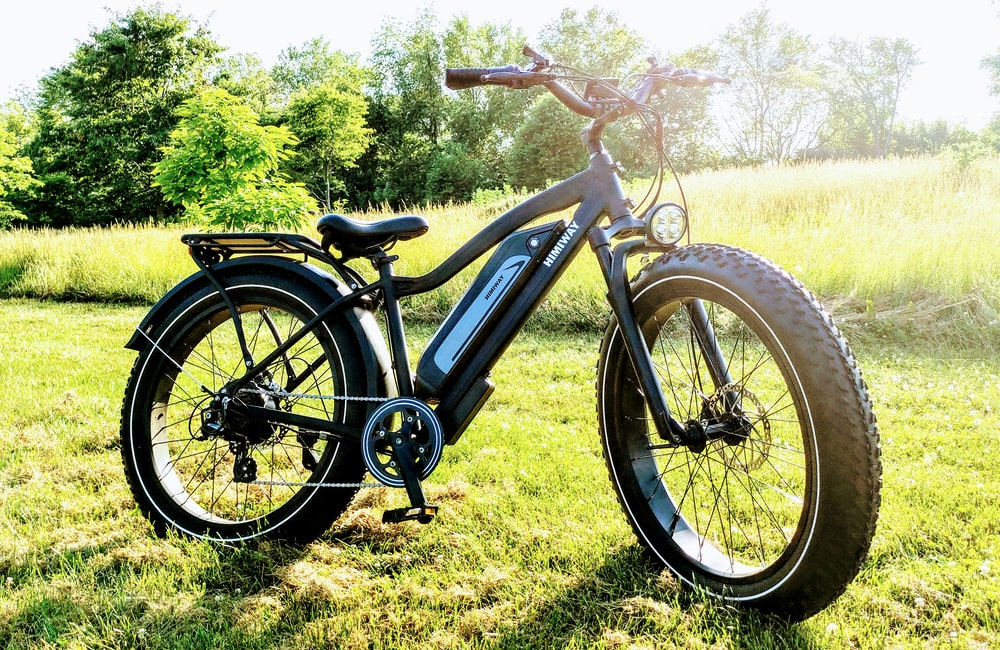 black and blue mountain bike on green grass field during daytime