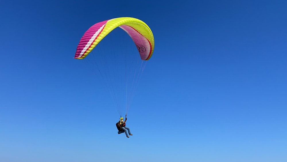 person in black jacket and black pants riding yellow and red parachute