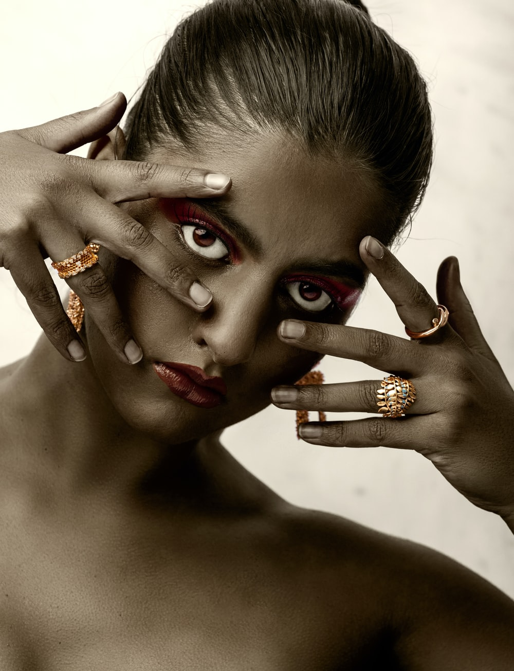 woman with red manicure wearing gold ring