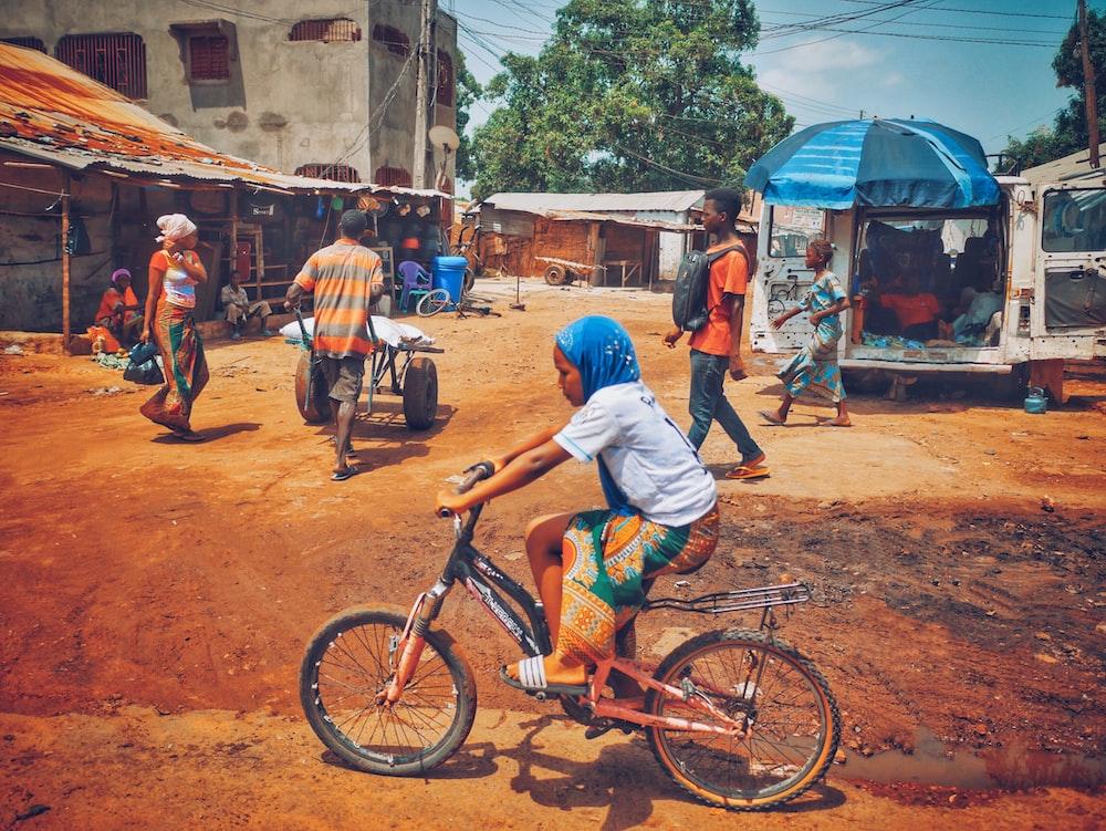 man in blue long sleeve shirt riding on orange bicycle during daytime