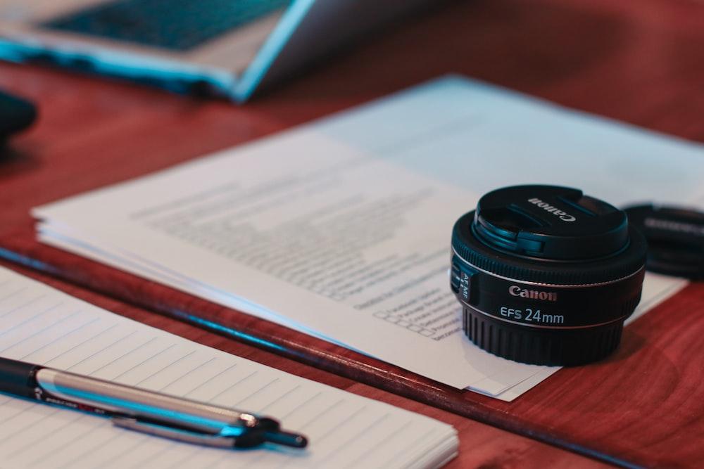 black camera lens on white printer paper