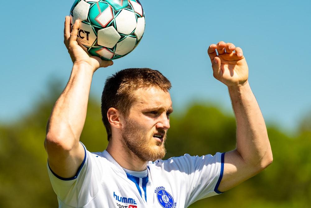 man in white nike soccer jersey holding soccer ball