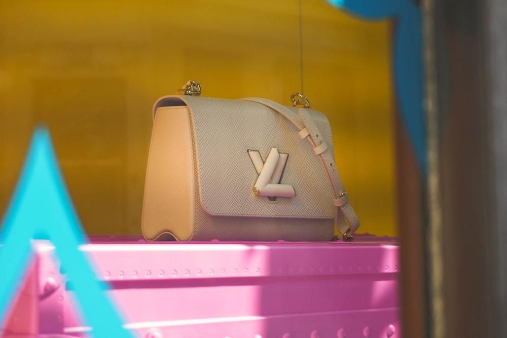 brown leather handbag on pink plastic drawer