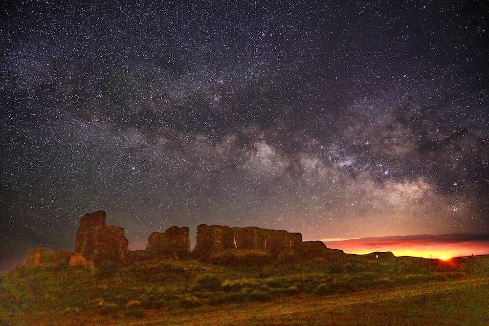 brown rock formation under starry night