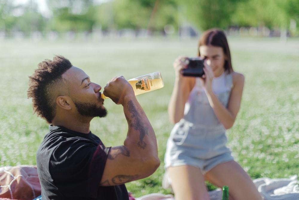 man in black crew neck t-shirt drinking beer