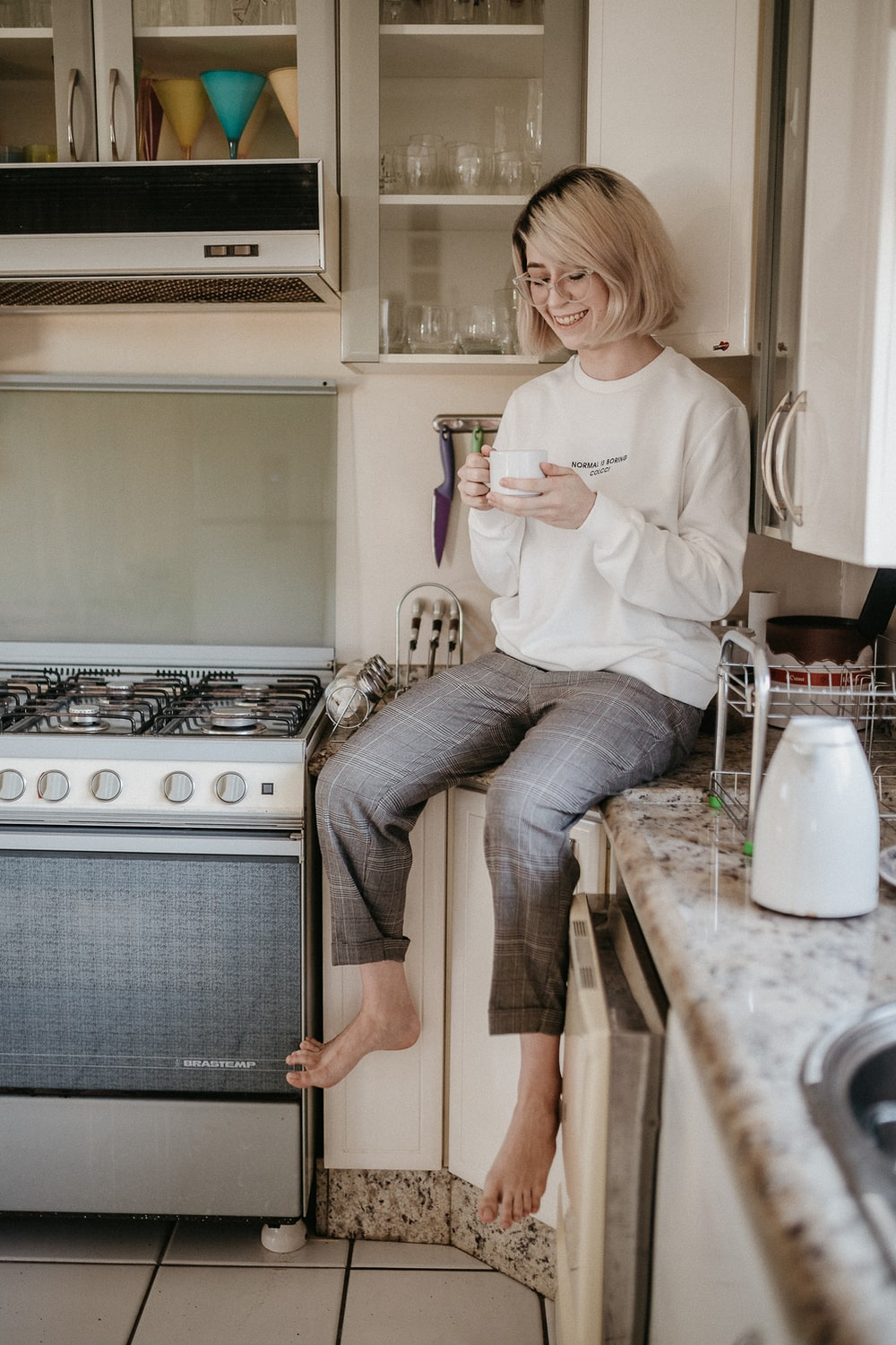 woman in white long sleeve shirt and blue denim jeans sitting on brown wooden table