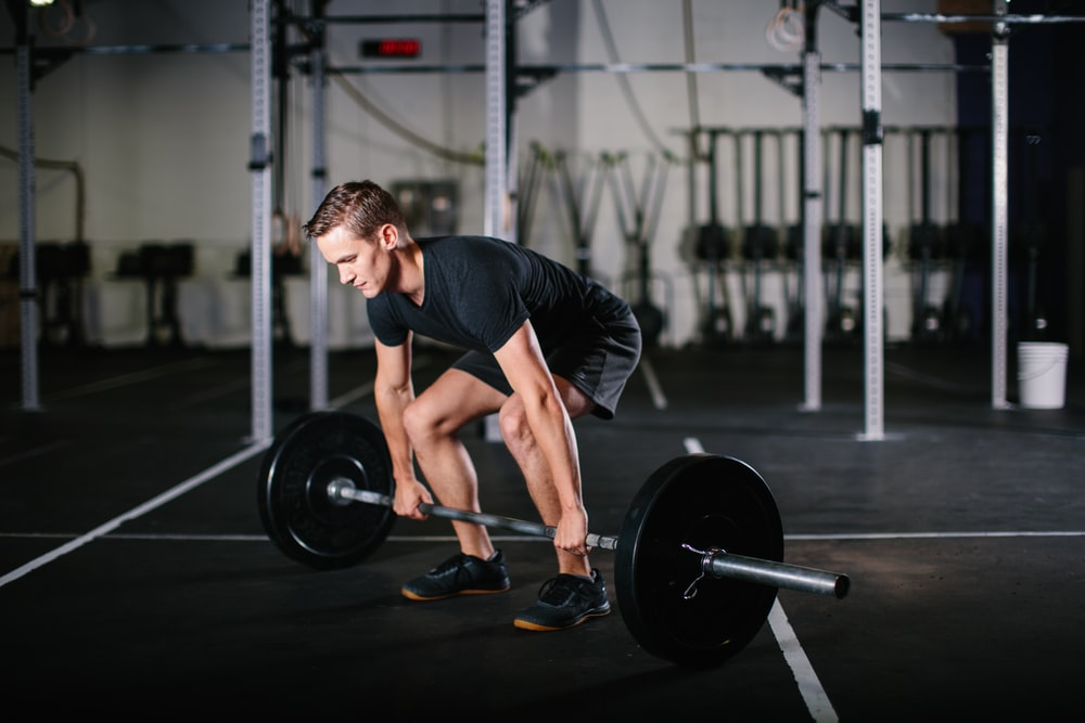 man in black t-shirt and black shorts holding black barbell