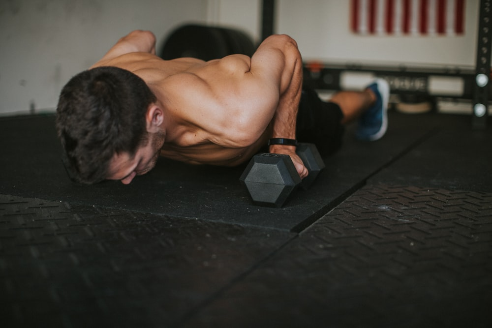 topless man lying on black floor