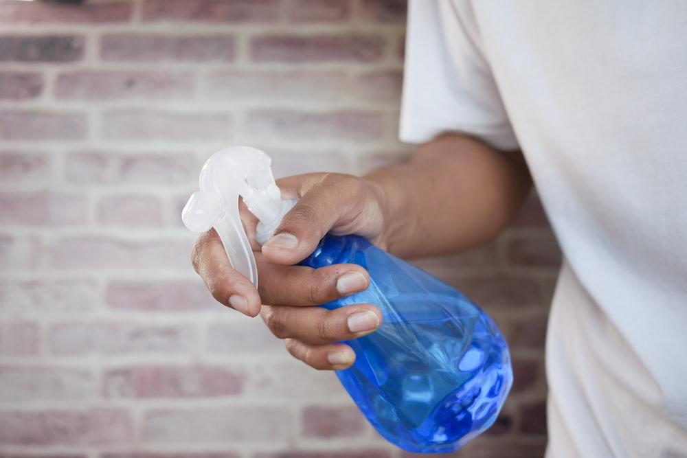 青いペットボトルを保持している白いシャツの人