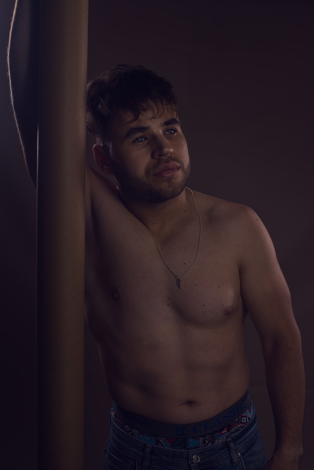 topless man wearing silver necklace
