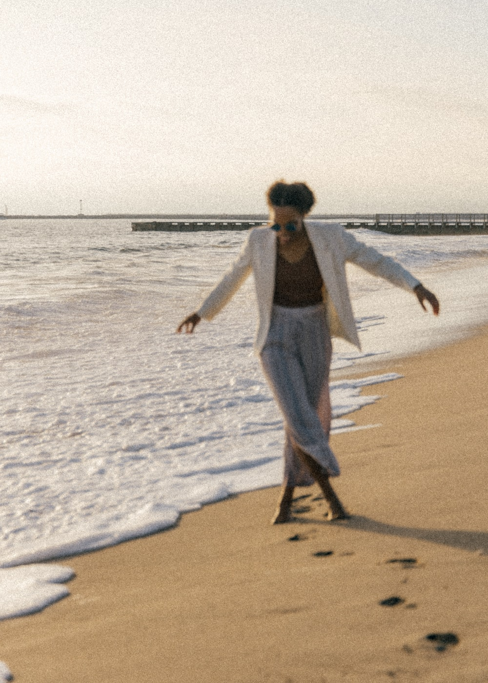 woman in white long sleeve shirt and gray pants walking on beach during daytime