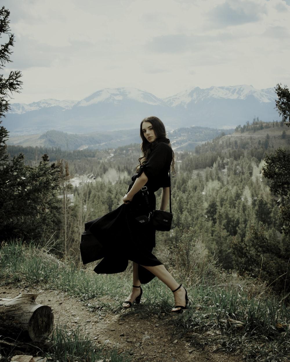 woman in black dress sitting on brown rock during daytime