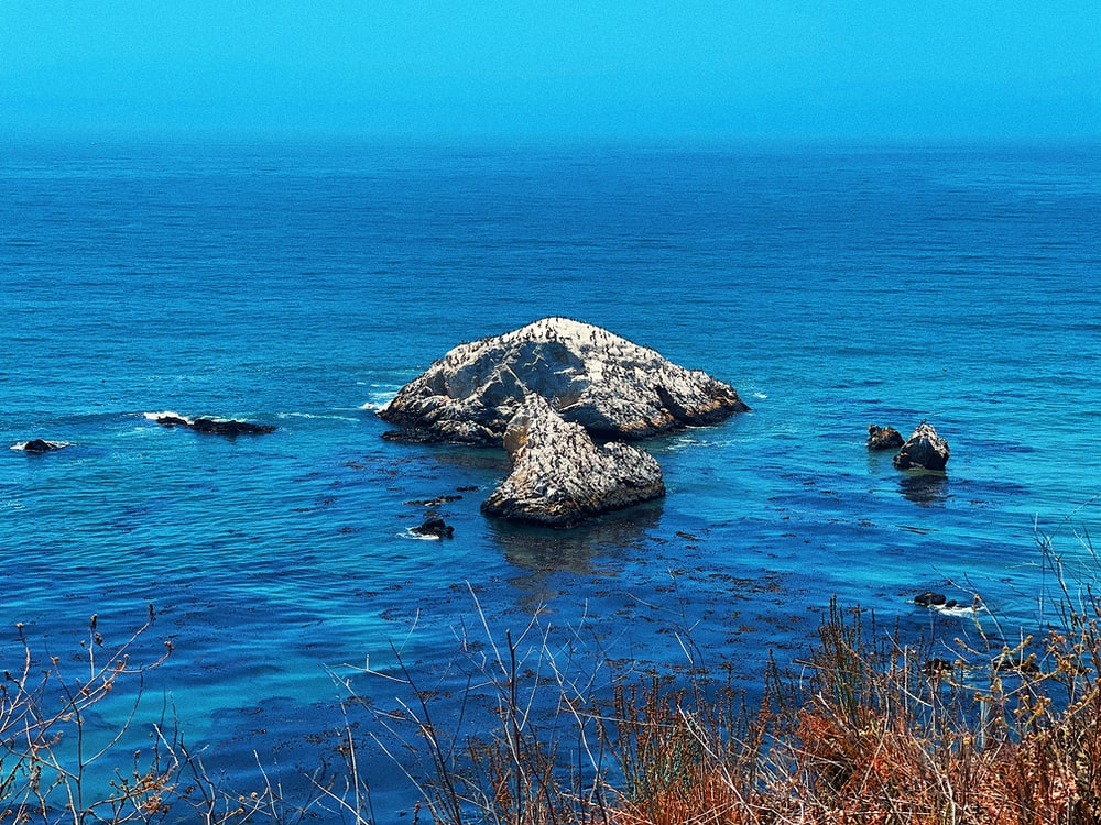 gray rock formation on blue sea during daytime