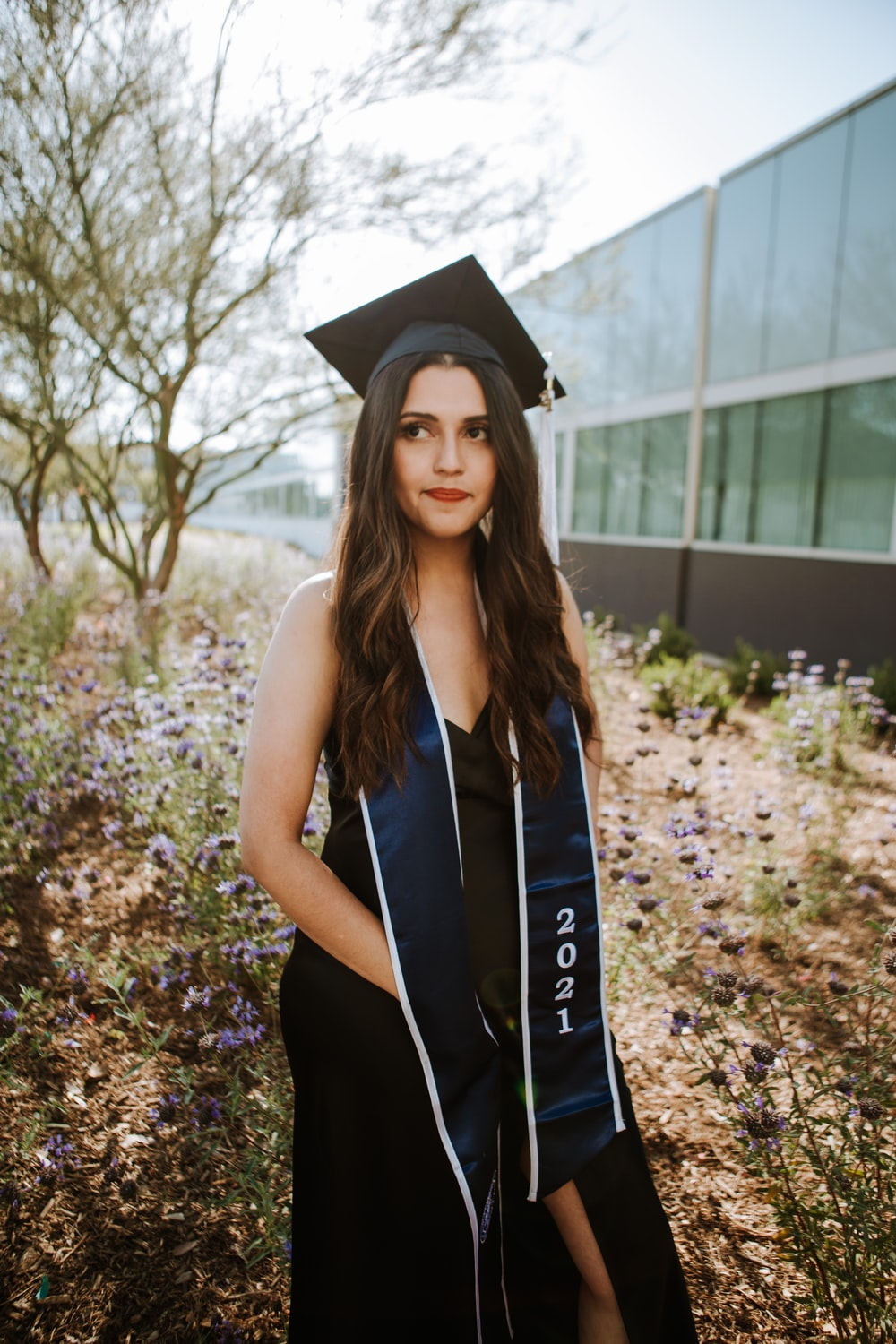 woman in black academic dress wearing black academic hat standing near green leaf trees during daytime