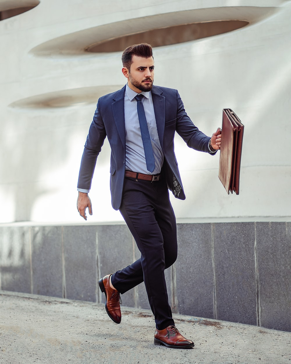 man in blue dress shirt and black pants standing on gray concrete stairs