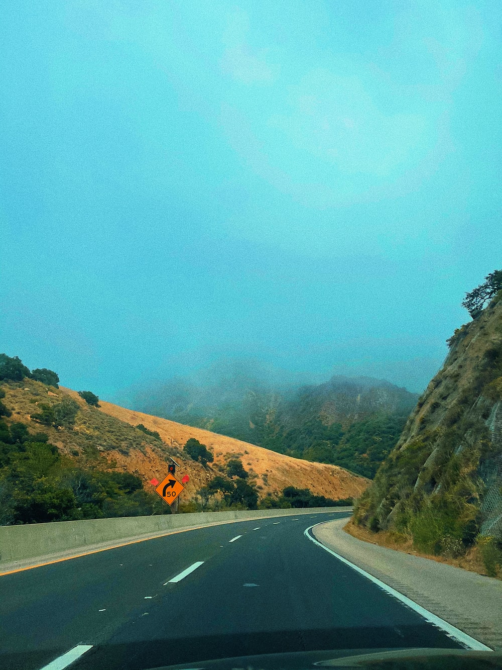 gray asphalt road near green mountain during daytime